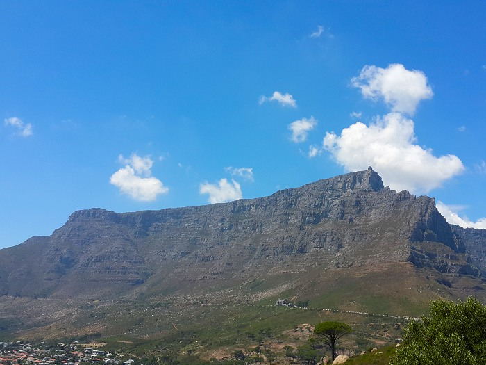 Looking up at Table Mountain,  a significant tourist attraction, with many visitors using the cableway or hiking to the top.